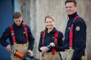 Tre brandmän, en kvinna i mitten och två män, iförda NÄRF:s larmställsbyxor med röda hängslen samt marinblå tröjor.